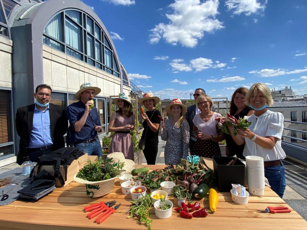 Moment convivial au potager d'entreprise CIC créé par Ciel mon radis. Les collaborateurs partagent les récoltes.